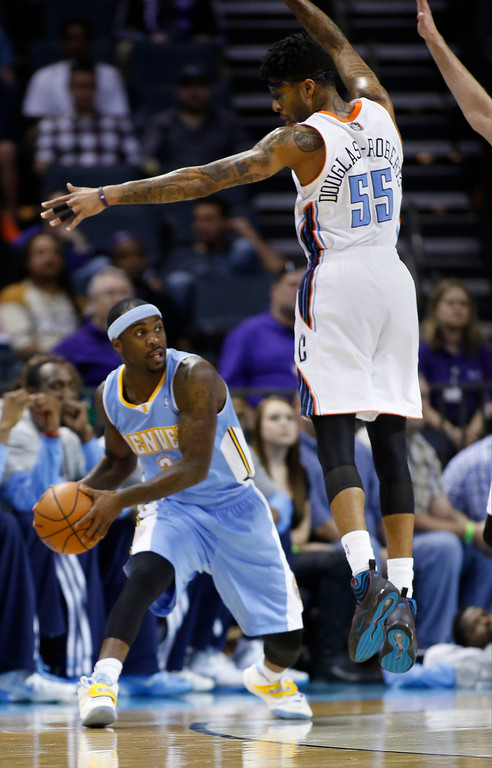 . Denver Nuggets guard Ty Lawson, left, looks to pass around Charlotte Bobcats guard Chris Douglas-Roberts during the first half of an NBA basketball game in Charlotte, N.C., Monday, March 10, 2014. (AP Photo/Nell Redmond)