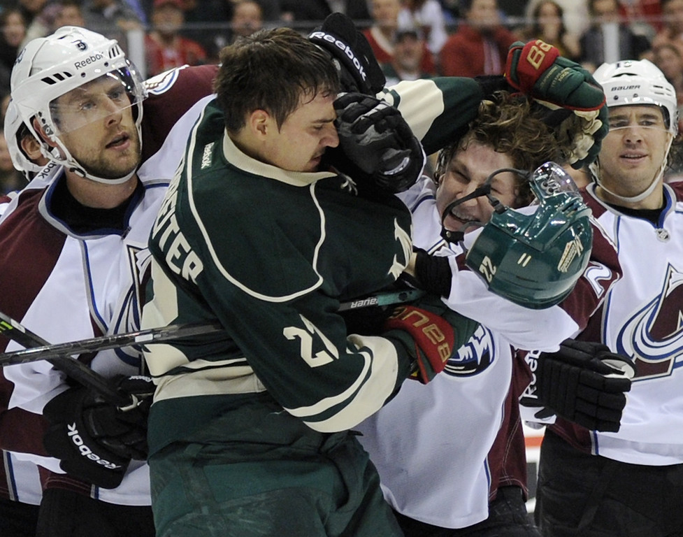. Nino Niederreiter #22 of the Minnesota Wild and Nathan MacKinnon #29 of the Colorado Avalanche fight during the second period of the game on November 29, 2013 at Xcel Energy Center in St Paul, Minnesota. (Photo by Hannah Foslien/Getty Images)
