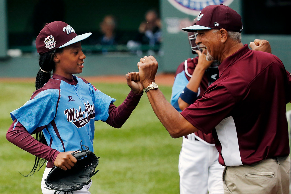 . Pennsylvania pitcher Mo\'ne Davis, left, celebrates with coach Leland Lott as she returns to the dugout at the end of the fifth inning during a baseball game against Tennessee in United States pool play at the Little League World Series tournament in South Williamsport, Pa., Friday, Aug. 15, 2014. Pennsylvania won 4-0, with Davis pitching a complete game two-hit shutout.(AP Photo/Gene J. Puskar)