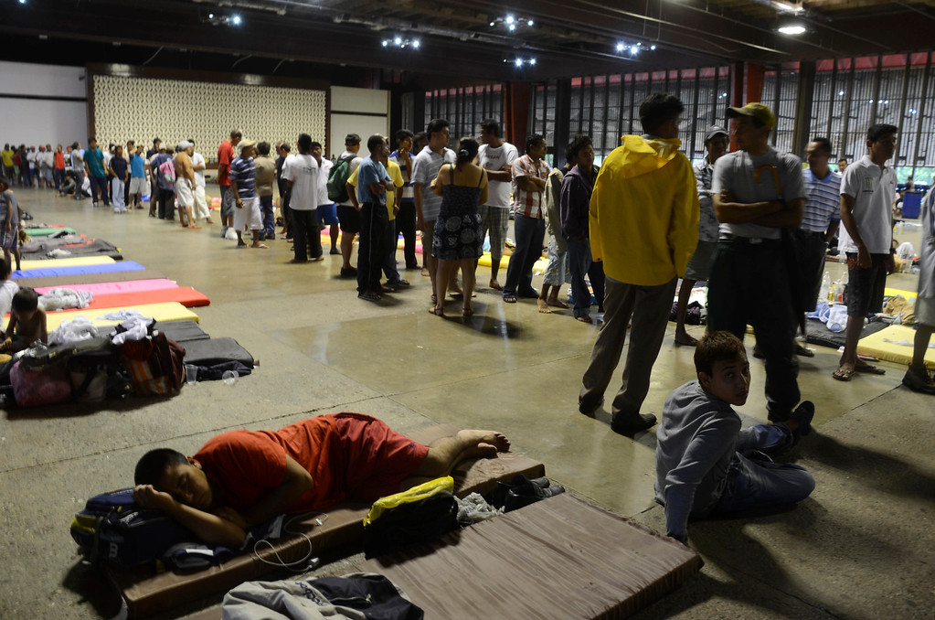 . People affected by Tropical Storm Manuel line up for assistance at a makeshift shelter in Acapulco, Mexico, Tuesday, Sept. 17, 2013. The death toll rose to 47 Tuesday from the unusual one-two punch of a tropical storm and a hurricane hitting Mexico at nearly the same time. Authorities scrambled to get help into, and stranded tourists out of, the cutoff resort city. (AP Photo/Bernandino Hernandez)