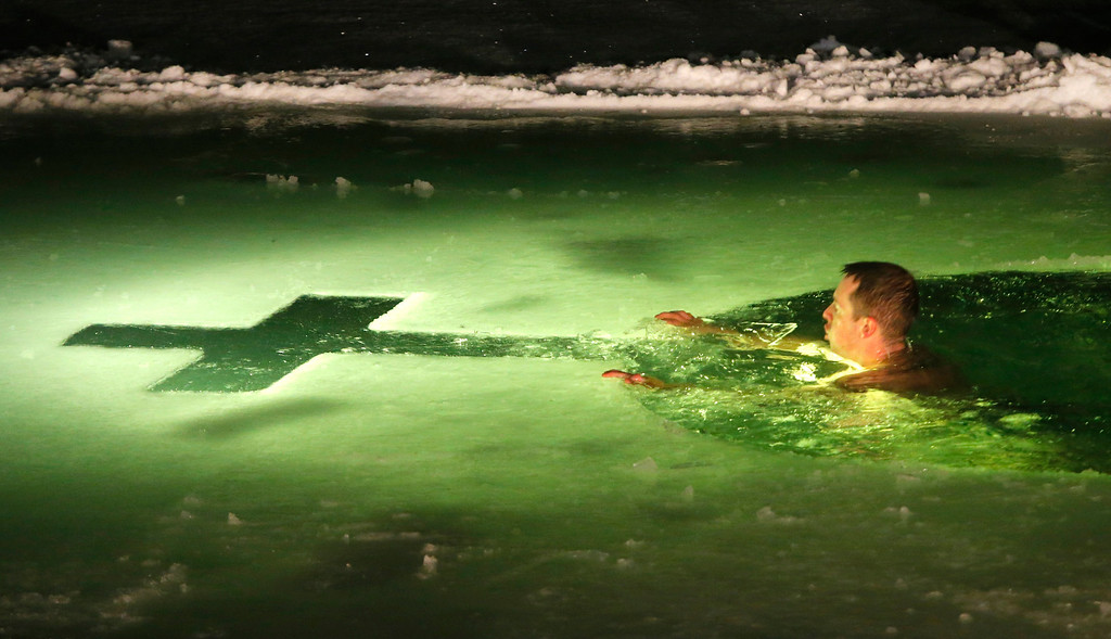 . A man swims in the ice cold water of a lake on the eve of Russian Orthodox Epiphany in Minsk, Belarus, late Saturday, Jan. 18, 2014. Orthodox Church believers celebrate Epiphany on Jan. 19. (AP Photo/Sergei Grits)
