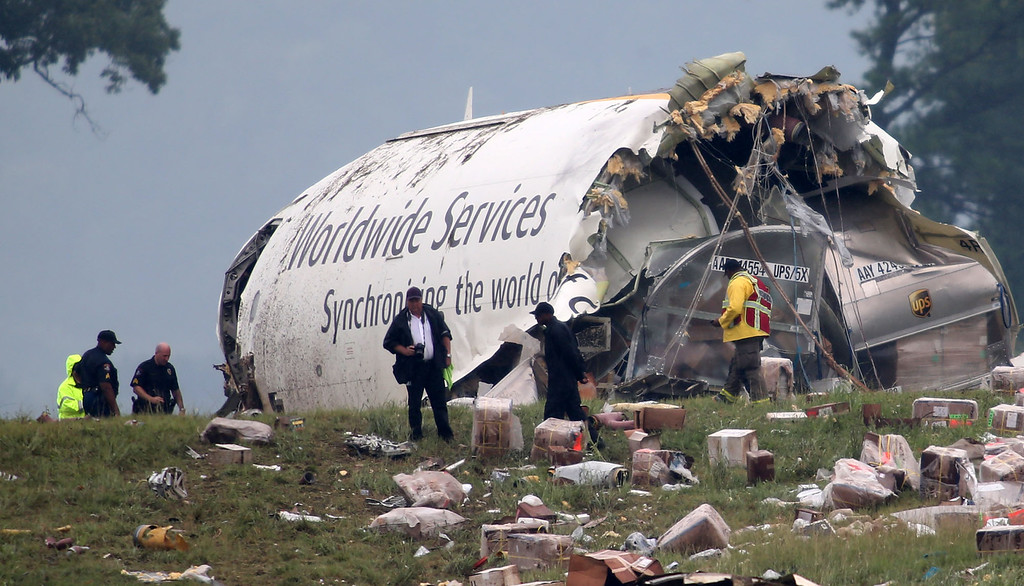 . Investigators look through debris of a UPS A300 cargo plane after it crashed on approach at Birmingham-Shuttlesworth International Airport, Wednesday, Aug. 14, 2013, in Birmingham, Ala.  (AP Photo/Hal Yeager)