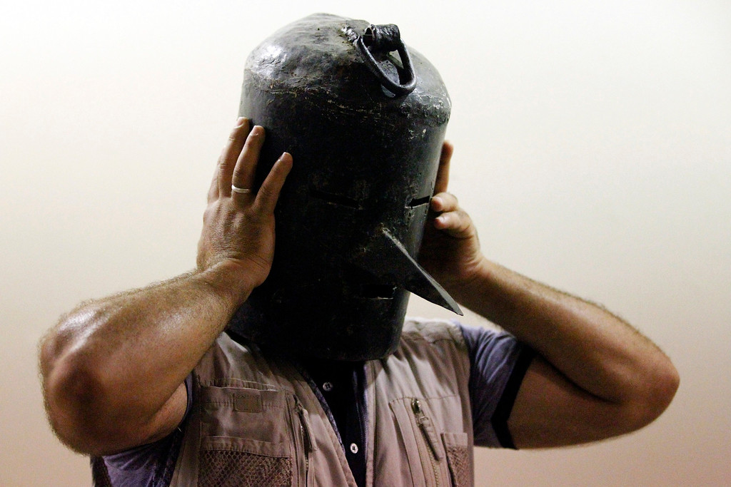 . A visitor tries on a metal mask, used as a torture device by the regime of Iraq\'s ousted leader Saddam Hussein, displayed at an exhibition gallery at the Martyrs Monument in Baghdad May 24, 2013.  REUTERS/Thaier al-Sudani