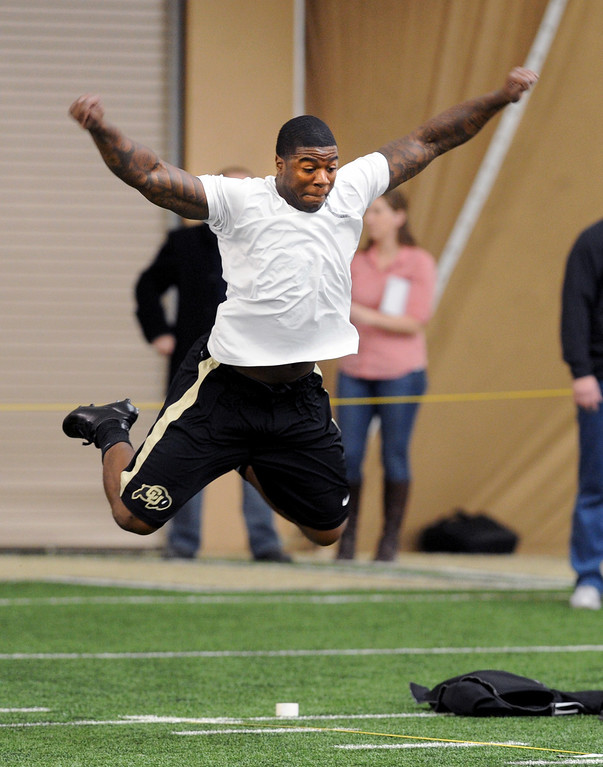 . Doug Rippy does his standing long jump for the scouts. Scouts from around the NFL  tested and watched University of Colorado football players during CU pro timing day on Wednesday. (Cliff Grassmick/Boulder Daily Camera)