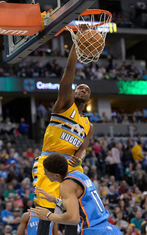 . Denver Nuggets small forward Jordan Hamilton (1) gets an easy dunk on Oklahoma City Thunder shooting guard Jeremy Lamb (11) during the second quarter December 17, 2013 at Pepsi Center. (Photo by John Leyba/The Denver Post)