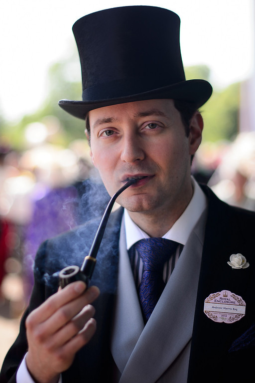 . Racegoer Andrew Harris smokes a pipe at Royal Ascot, in Berkshire, west of London, on June 17, 2014. AFP PHOTO / LEON NEAL/AFP/Getty Images