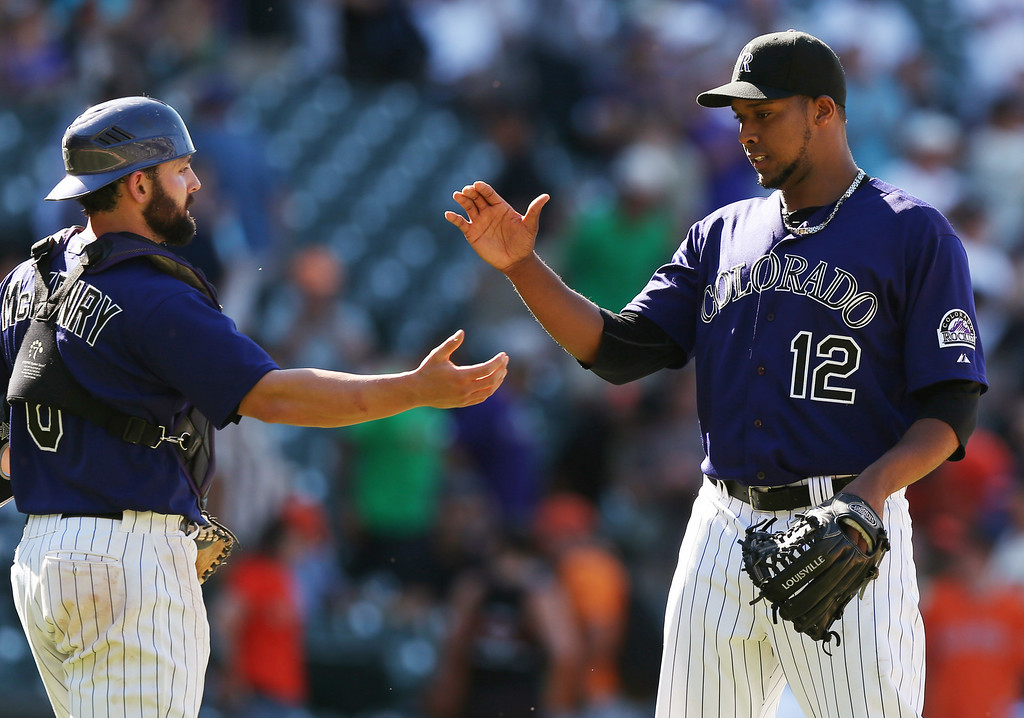 . Colorado Rockies catcher Michael McKenry, left, congratulates relief pitcher Juan Nicasio after he retired the San Francisco Giants in the ninth inning of the Rockies\' 9-2 victory in a baseball game in Denver on Wednesday, Sept. 3, 2014. (AP Photo/David Zalubowski)