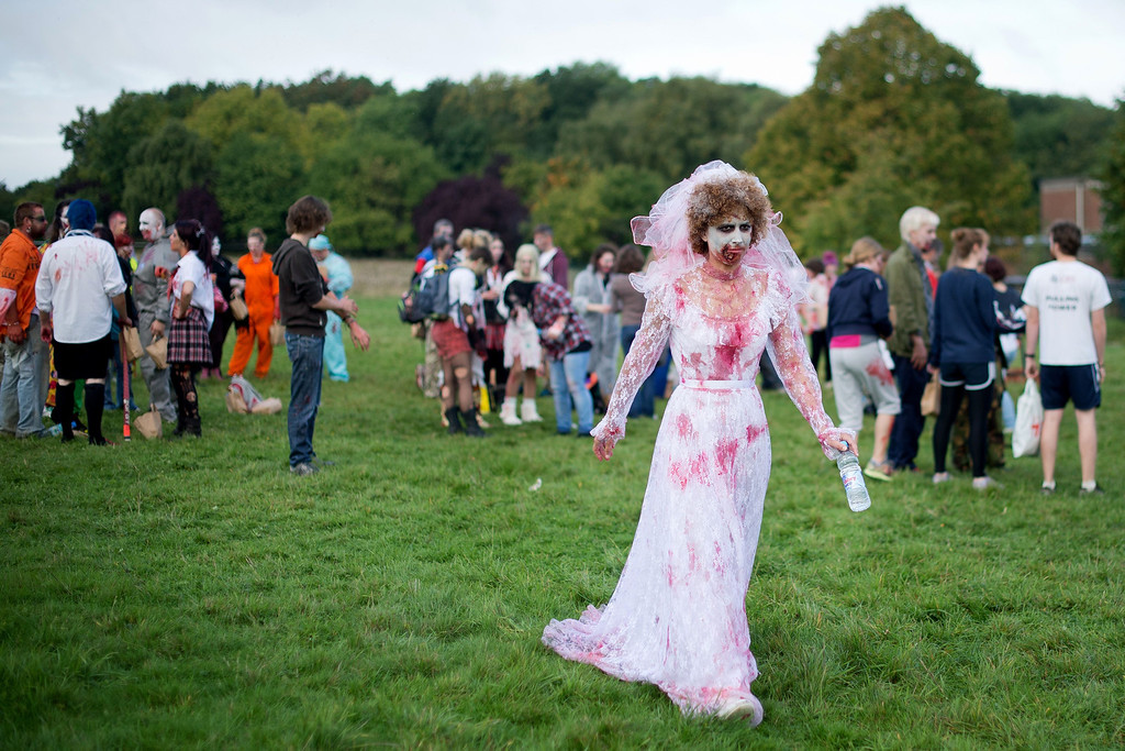 ". A volunteer zombie bride prepares to take part in one of Britain\'s biggest horror events, the ""Zombie Evacuation Race\"" at Carver Barracks near Saffron Walden, England, on October 5, 2013. The race sees thousands of participants attempt to complete a gruelling 5 kilometre cross-country run, while evading \""zombies\"", intent on snatching the three life-line strips hanging from every runner\'s waist.  Those who manage to get through with any strips remaining are named as survivors while those without take home an \""infected\"" badge.  LEON NEAL/AFP/Getty Images"