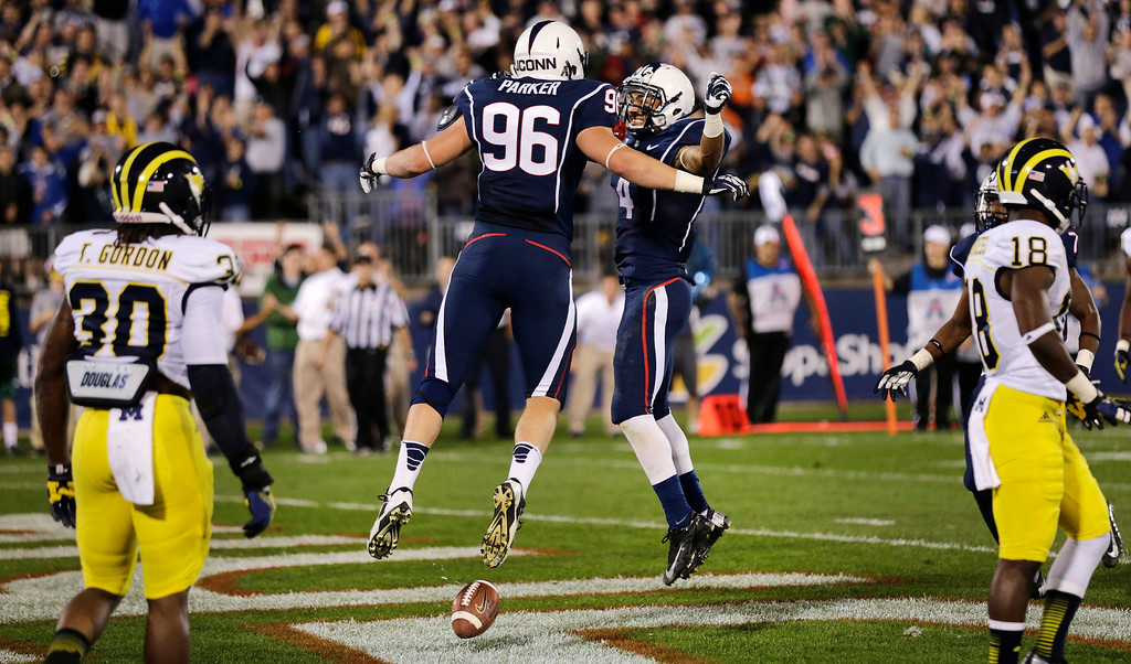 . Connecticut tight end Spencer Parker (96) celebrates his touchdown with wide receiver Deshon Foxx namduring the second quarter of an NCAA college football game against Michigan, Saturday, Sept. 21, 2013, in East Hartford, Conn. (AP Photo/Charles Krupa)