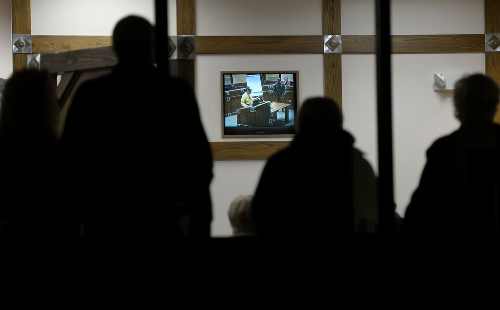 . The overflow crowd watches the fire update via a television outside of the city council chambers. Dozens of evacuees and Estes Park residents packed the city council chambers in the Estes Park Town Hall to get an update on the Fern Lake Fire burning in Rocky Mountain National Park on December 2, 2012.  Helen H. Richardson, The Denver Post