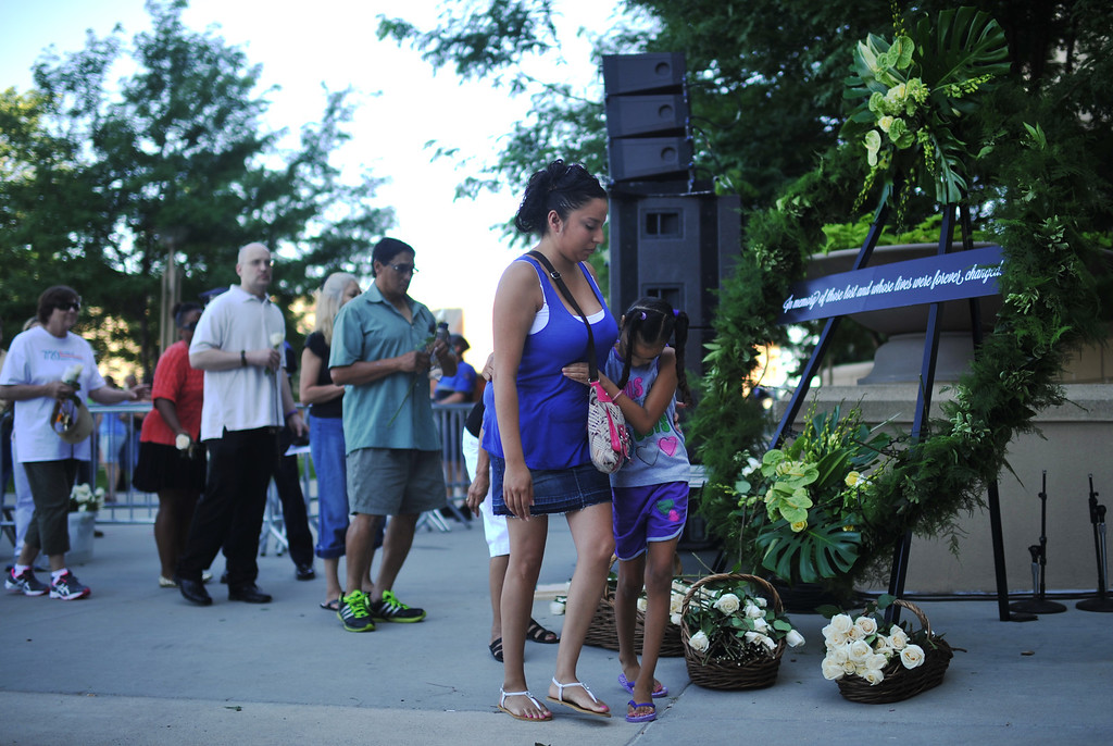 . AURORA, CO. - July 20: People place roses outside the Aurora Municipal Center, marking the first anniversary of the deaths of 12 people and the injury of at least 70 others in a mass shooting that forever changed an entire community. Aurora, Colorado. July 20, 2013.  (Photo By Hyoung Chang/The Denver Post)