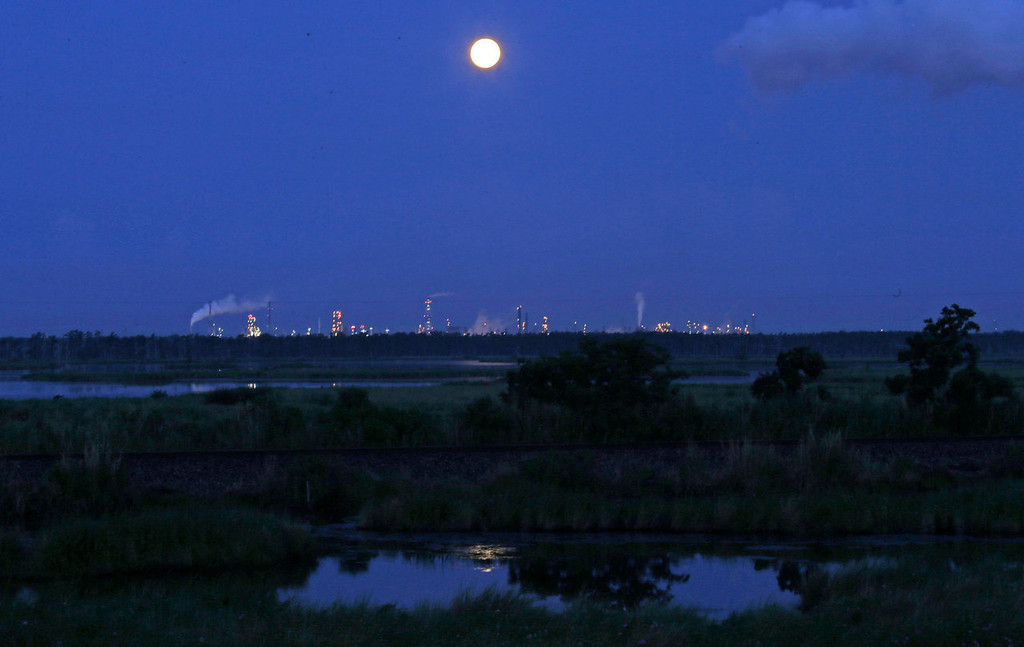 ". The larger-than-normal full moon referred to as a ""super moon\"" is seen setting beyond a refinery in Norco, Louisiana on Sunday, June 23, 2013.  (AP Photo/Gerald Herbert)"