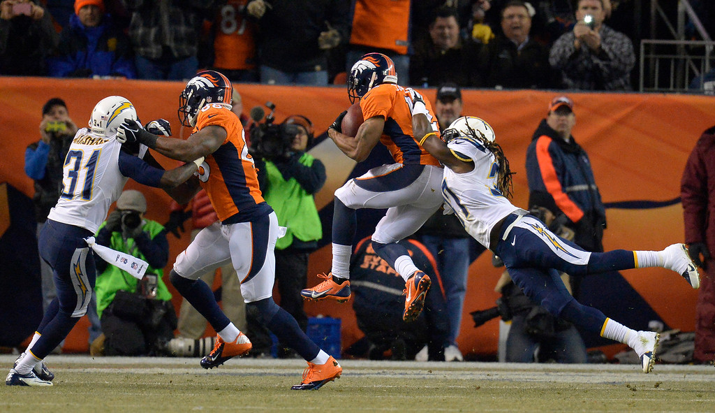 . Denver Broncos wide receiver Andre Caldwell (12) jumps into the end zone to score his second touchdown of the game during the fourth quarter. The Denver Broncos vs. the San Diego Chargers at Sports Authority Field at Mile High in Denver on December 12, 2013. (Photo by John Leyba/The Denver Post)