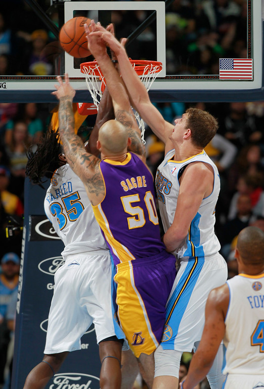 . Los Angeles Lakers center Robert Sacre, center, has his shot blocked by Denver Nuggets forward Kenneth Faried, left, as center Timofey Mozgov, of Russia, covers  in the fourth quarter of the Nuggets\' 134-126 victory in an NBA basketball game in Denver on Friday, March 7, 2014. (AP Photo/David Zalubowski)