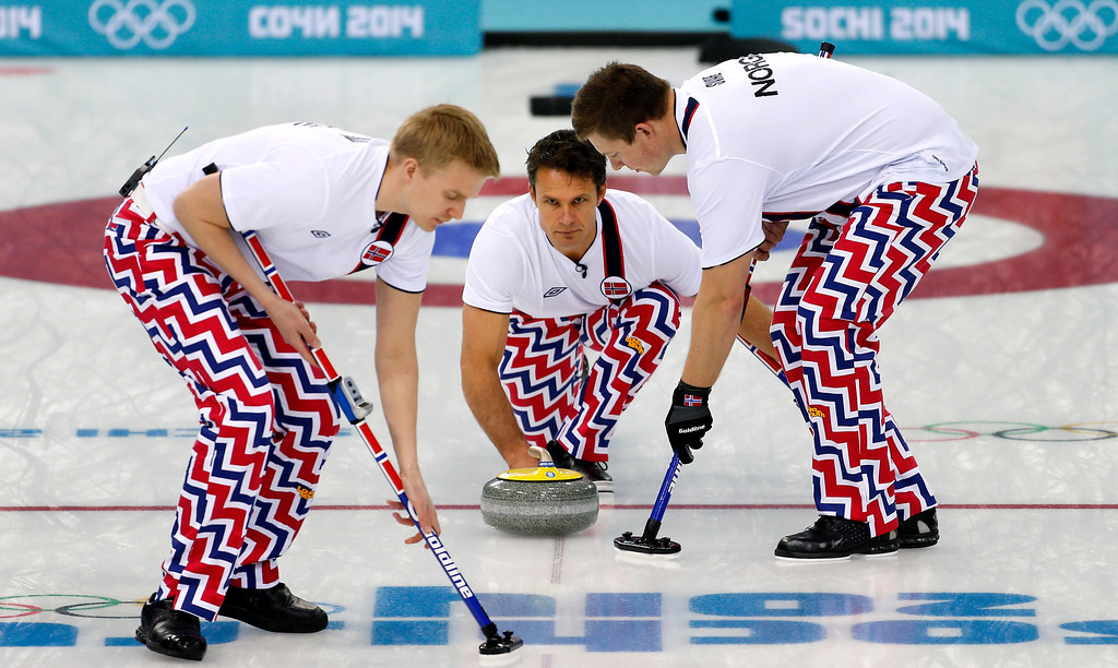 . Norway\'s skip Thomas Ulsrud delivers the rock to sweepers Haavard Vad Petersson, left, and Christoffer Svae, right, during the men\'s curling match against Britain at the 2014 Winter Olympics, Sunday, Feb. 16, 2014, in Sochi, Russia. (AP Photo/Wong Maye-E)