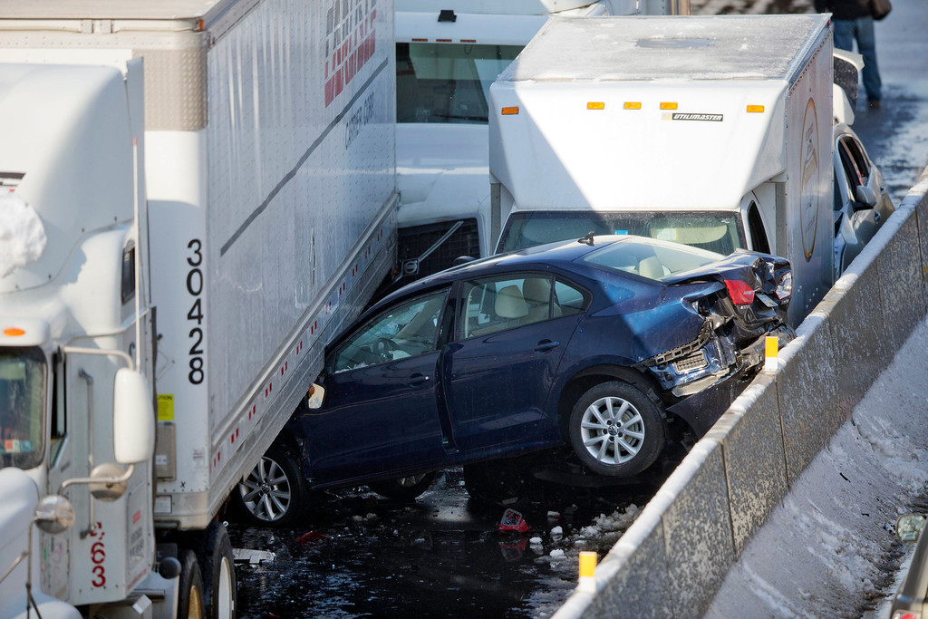 . Vehicles are piled up from an accident Friday, Feb. 14, 2014, in Bensalem, Pa. Traffic accidents involving multiple tractor-trailers and dozens of cars have completely blocked one side of the Pennsylvania Turnpike outside Philadelphia and caused some injuries. (AP Photo/Matt Rourke)