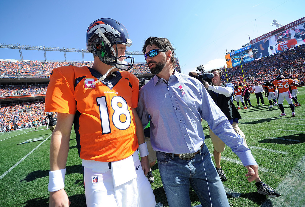 . Todd Helton, who retired from the Colorado Rockies after the past baseball season, speaks with Denver Broncos quarterback Peyton Manning (18) before the start of the game. The Broncos honored recently retired Helton with a Broncos jersey before the game.   (Photo by John Leyba/The Denver Post)