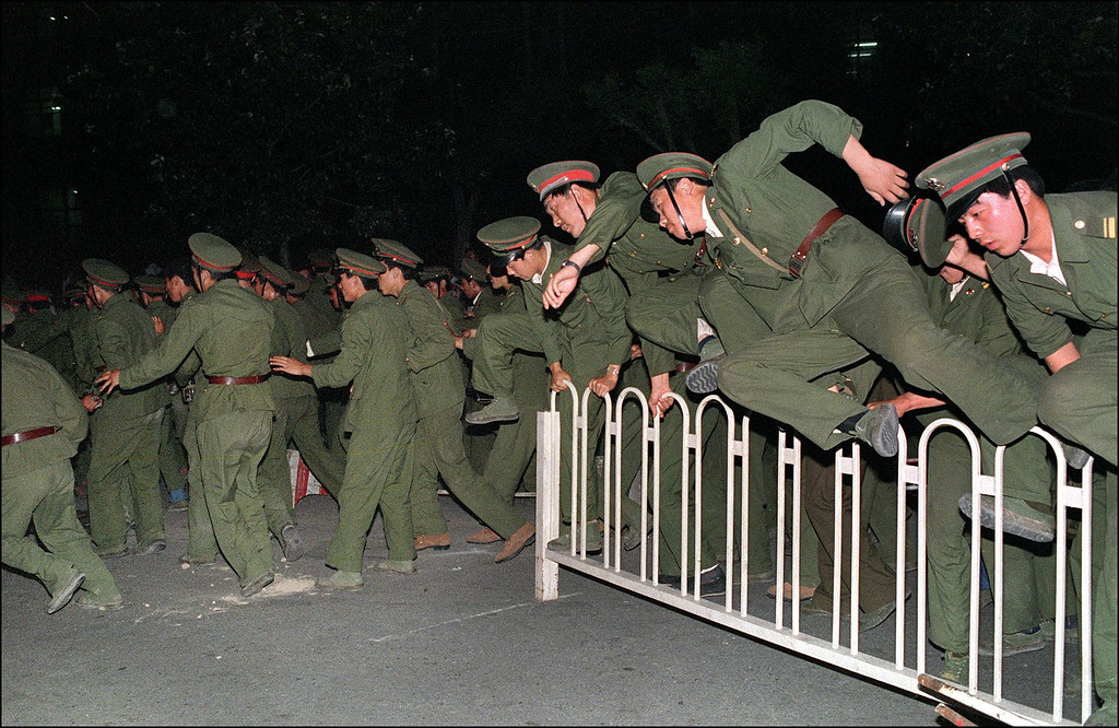 . People Liberation Army (PLA) soldiers  leap over a barrier on Tiananmen Square in central Beijing 04 June 1989 during heavy clashes with people and dissident students.  (THOMAS CHENG/AFP/Getty Images)