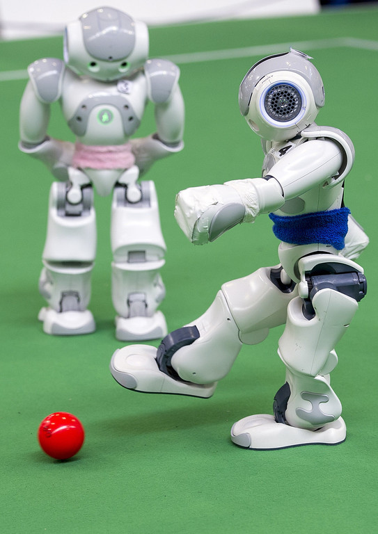 . MAGDEBURG, GERMANY - APRIL 26:  Two teams of robots play against each other in soccer at the 2013 RoboCup German Open tournament on April 26, 2013 in Magdeburg, Germany. The robots, which are a model called Nao, manufactured by Aldebaran Robotics, perform autonomously and communicate with one another via WLAN. The three-day tournament is hosting 43 international teams and 158 German junior teams that compete in a variety of disciplines, including soccer, rescue and dance.  (Photo by Jens Schlueter/Getty Images)