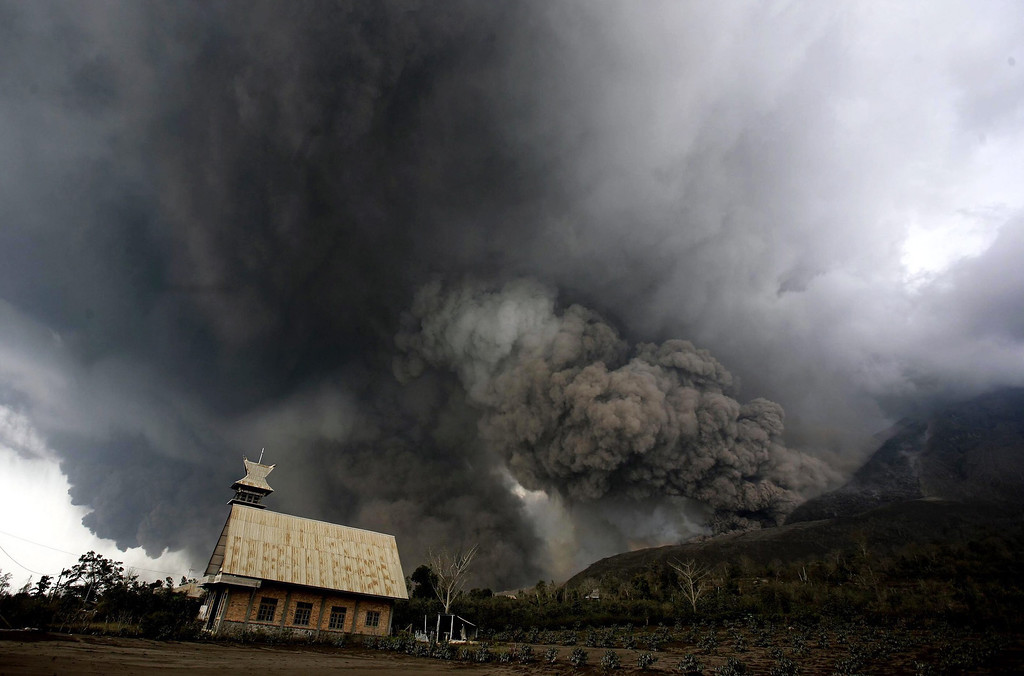 . Mount Sinabung spews volcanic materials in Karo, North Sumatra, Indonesia, 01 February 2014. At least 14 people were killed when a volcano on the Indonesian island of Sumatra spewed lava and hot gas, an aid worker said. The eruption of Mount Sinabung came a day after the National Disaster Management Agency said residents living farther than 5 kilometers from the peak were being allowed to return to their homes after a lull in activity.  EPA/CHAIRALY