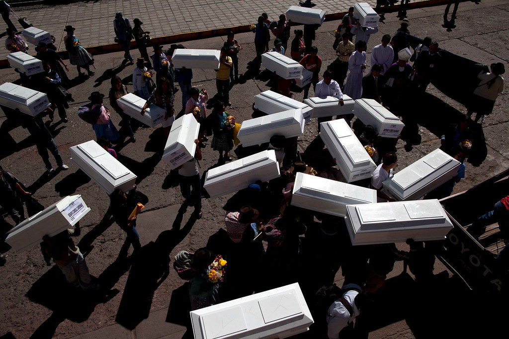 . After attending a brief memorial service marking the return of their relatives\' exhumed remains, family members carry coffins containing the remains through the main square in Ayacucho, Peru, before returning to Chaca for a mass burial.  The remains were exhumed in 2012 from a mass grave and released to family members on June 13, 2013. The victims were killed in 1988 by Shining Path militants in retaliation for forming a self-defense committee. (AP Photo/Rodrigo Abd)