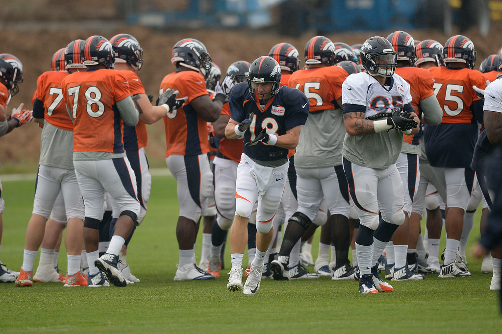 . Denver Broncos quarterback Peyton Manning (18) claps his hand as he heads to drills on day seven of the Denver Broncos 2014 training camp July 31, 2014 at Dove Valley. (Photo by John Leyba/The Denver Post)