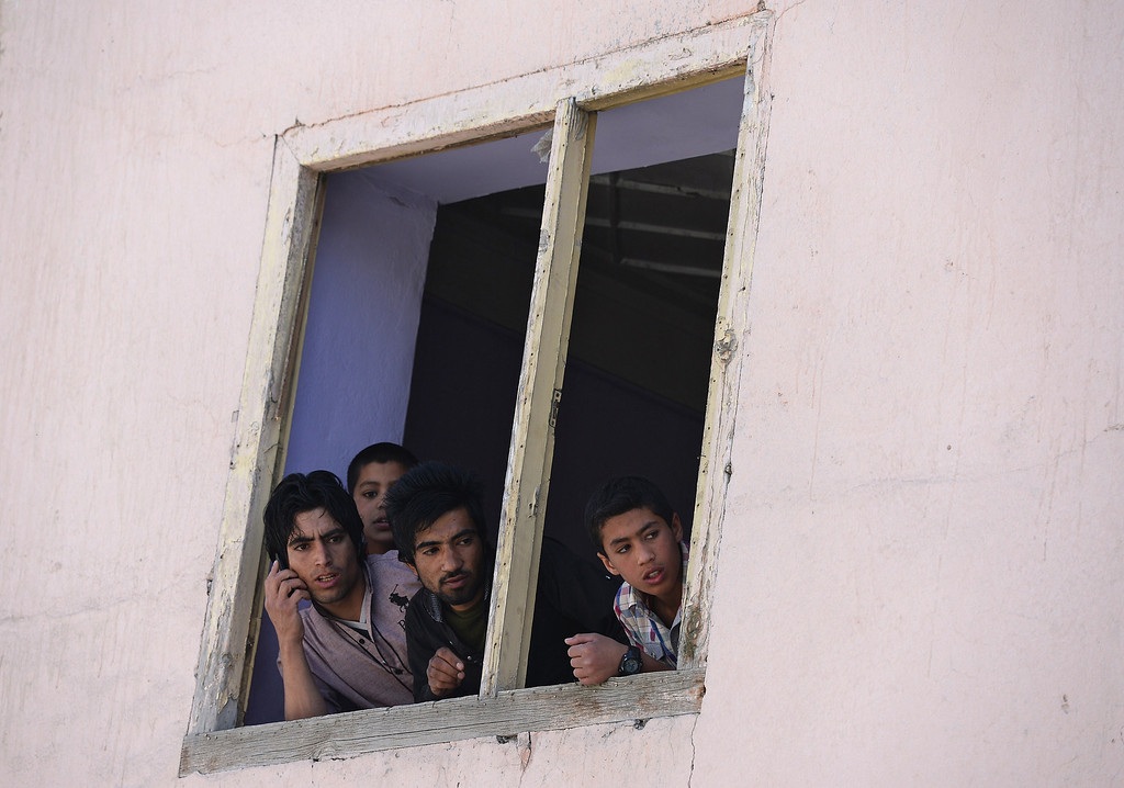 . Afghan boys look on through a window near the site of a suicide attack in Kabul on May 16, 2013. AFP PHOTO/ Massoud HOSSAINI/AFP/Getty Images