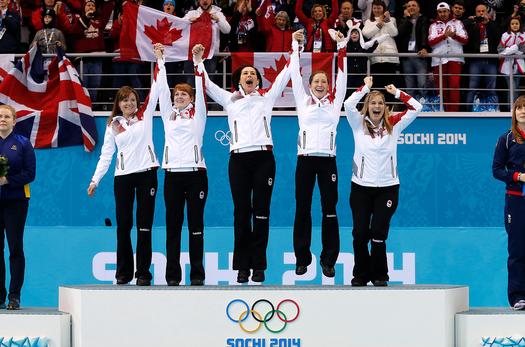 . Canada\'s women\'s curling team as seen from left to right, Kirsten Wall, Dawn McEwen, Jill Officer, Kaitlyn Lawes and skip Jennifer Jones, celebrate during the flower ceremony after winning the women\'s curling gold medal game against Sweden at the 2014 Winter Olympics, Thursday, Feb. 20, 2014, in Sochi, Russia. (AP Photo/Wong Maye-E)