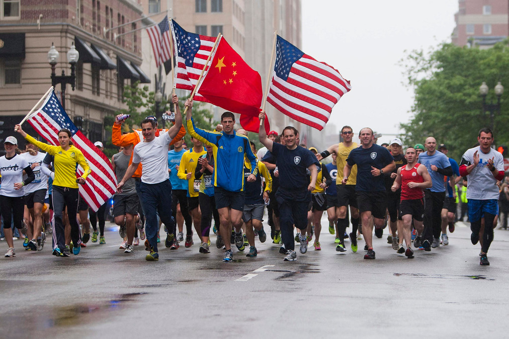 """. Runners carry American flags and a Chinese flag as they approach the finish line after completing the final mile of the Boston Marathon course during \""""#onerun\"""" in Boston, Massachusetts, May 25, 2013.   REUTERS/Dominick Reuter"""