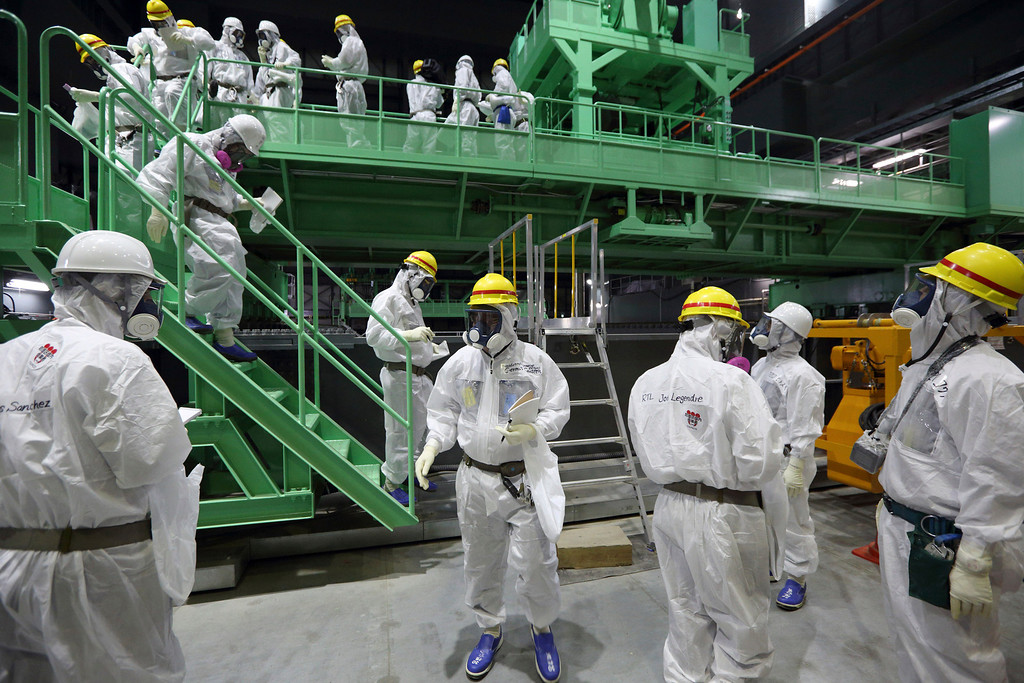 . Members of the media and Tokyo Electric Power Co. employees wearing protective suits and masks walk down the steps of a fuel handling machine after looking at the spent fuel pool inside the building housing the Unit 4 reactor at the Fukushima Dai-ichi nuclear power plant in Okuma, Fukushima Prefecture, Japan, Thursday, Nov. 7, 2013.  (AP Photo/Tomohiro Ohsumi, Pool)