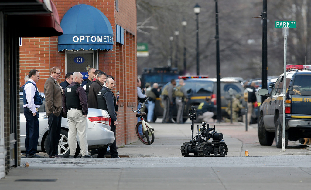 . A police robot moves along the street while police search for a suspect in two shootings that killed four and injured at least  two on, Wednesday, March 13, 2013, in Herkimer, N.Y. (AP Photo/Mike Groll)