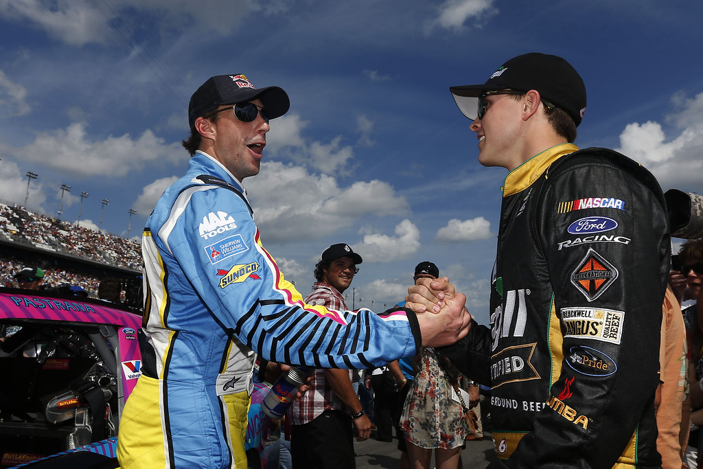 . DAYTONA BEACH, FL - FEBRUARY 23: Travis Pastrana, driver of the #60 Roush-Fenway Racing Ford, speaks with Trevor Bayne, driver of the #6 Cargill Ford, on the grid before the NASCAR Nationwide Series DRIVE4COPD 300 at Daytona International Speedway on February 23, 2013 in Daytona Beach, Florida.  (Photo by Chris Graythen/Getty Images)