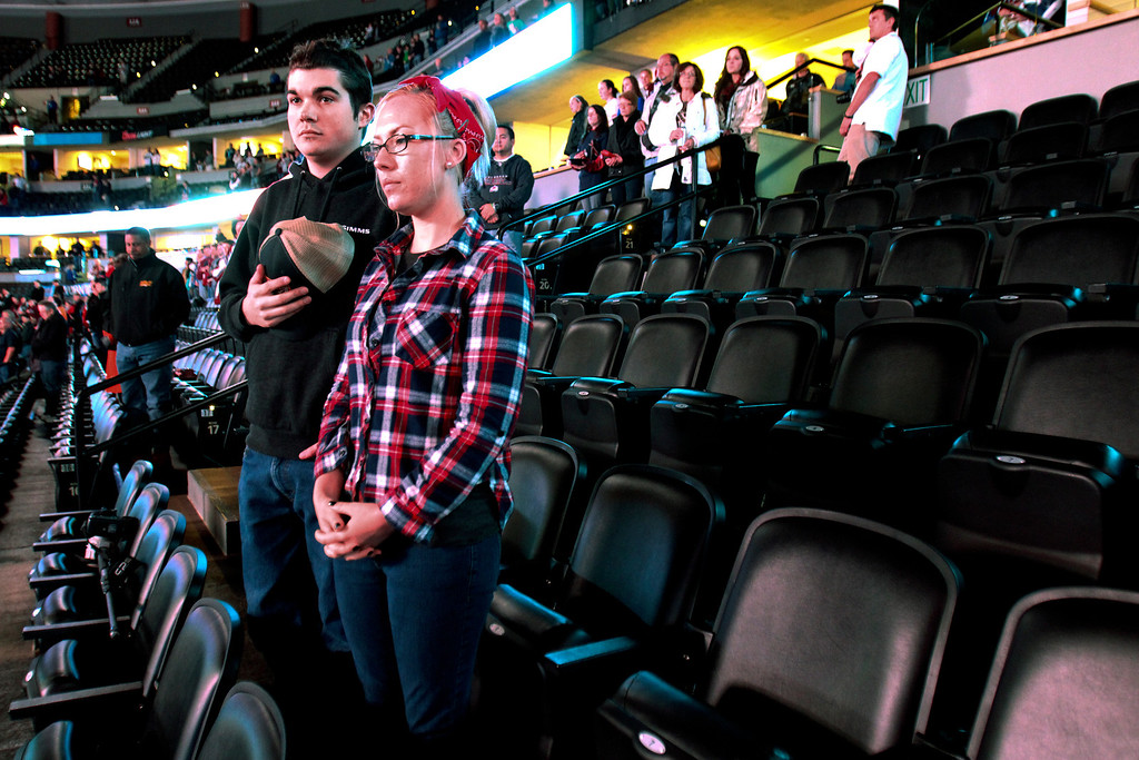 . Cody Hoeckelberg and Stephanie Mack stand for a moment of silence for the victims of explosions at the Boston Marathon before an NHL hockey game between the Columbus Blue Jackets and the Colorado Avalanche on Monday, April 15, 2013 in Denver. (AP Photo/Barry Gutierrez)