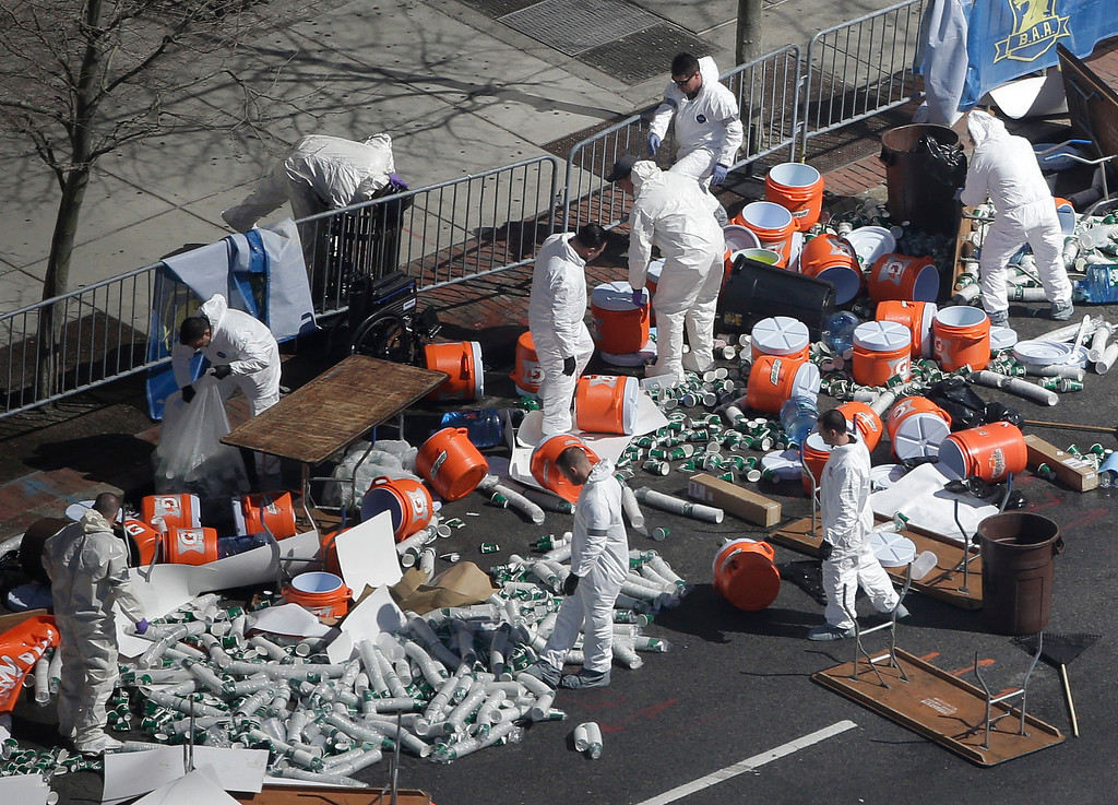 . Investigators comb through the post finish line area of the Boston Marathon at Boylston Street, two days after two bombs exploded just before the finish line, Wednesday, April 17, 2013, in Boston. (AP Photo/Julio Cortez)