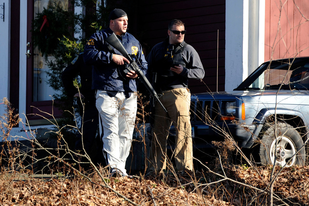 . Law enforcement canvass an area following a shooting at the Sandy Hook Elementary School in Newtown, Conn., about 60 miles (96 kilometers) northeast of New York City, Friday, Dec. 14, 2012. An official with knowledge of Friday\'s shooting said 27 people were dead, including 18 children.  (AP Photo/Jessica Hill)