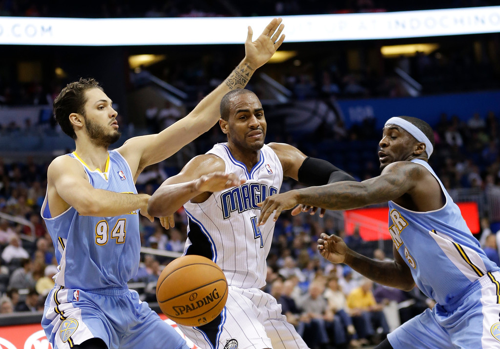 . Orlando Magic\'s Arron Afflalo, center, loses the ball as he tries to drive between Denver Nuggets\'s Evan Fournier (94) and Ty Lawson (3) during the second half of an NBA basketball game in Orlando, Fla., Wednesday, March 12, 2014. Denver won 120-112. (AP Photo/John Raoux)