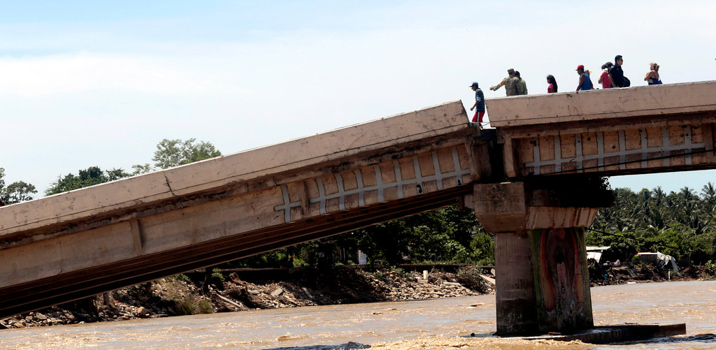 . People cross a collapsed bridge destroyed by Hurricane Ingrid in Coyuca de Benitez area, Guerrero state, Mexico, on September 18, 2013. Hurricane Ingrid weakened to tropical storm strength as it made landfall on the northeastern coast in the morning while the Pacific coast was reeling from the remnants of Tropical Storm Manuel, which dissipated after striking on the eve. Thousands of people were evacuated on both sides of the country as the two storms set off landslides and floods that damaged bridges, roads and homes. Pedro PARDO/AFP/Getty Images