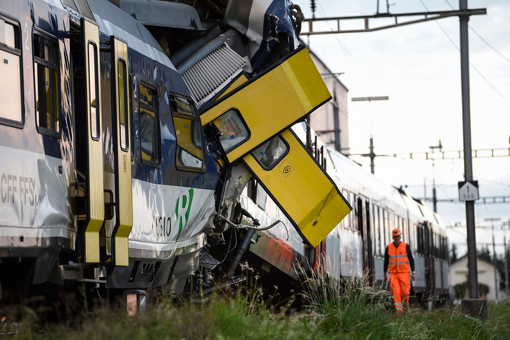 . Rescue personnel work at the site where two passenger trains collided head-on in Granges-pres-Marnand, western Switzerland, Monday, July 29, 2013. Police say at least 44 people were injured, four of them seriously. (AP Photo/Keystone, Laurent Gillieron)