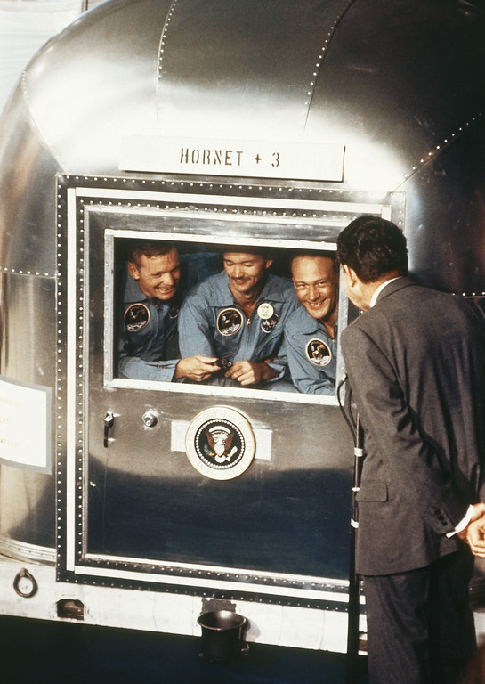 ". FILE - In this July 24, 1969 file photo, President  Richard Nixon, right, greets the Apollo 11 astronauts in the quarantine van on board the U.S.S. Hornet after splashdown and recovery. The Apollo 11 crew from left are Neil Armstrong, Michael Collins, and Edwin ""Buzz\"" Aldrin. Armstrong and Aldrin became the first men to walk on the moon after blastoff from Cape Kennedy, Fla., on July 16, 1969. (AP Photo, File)"