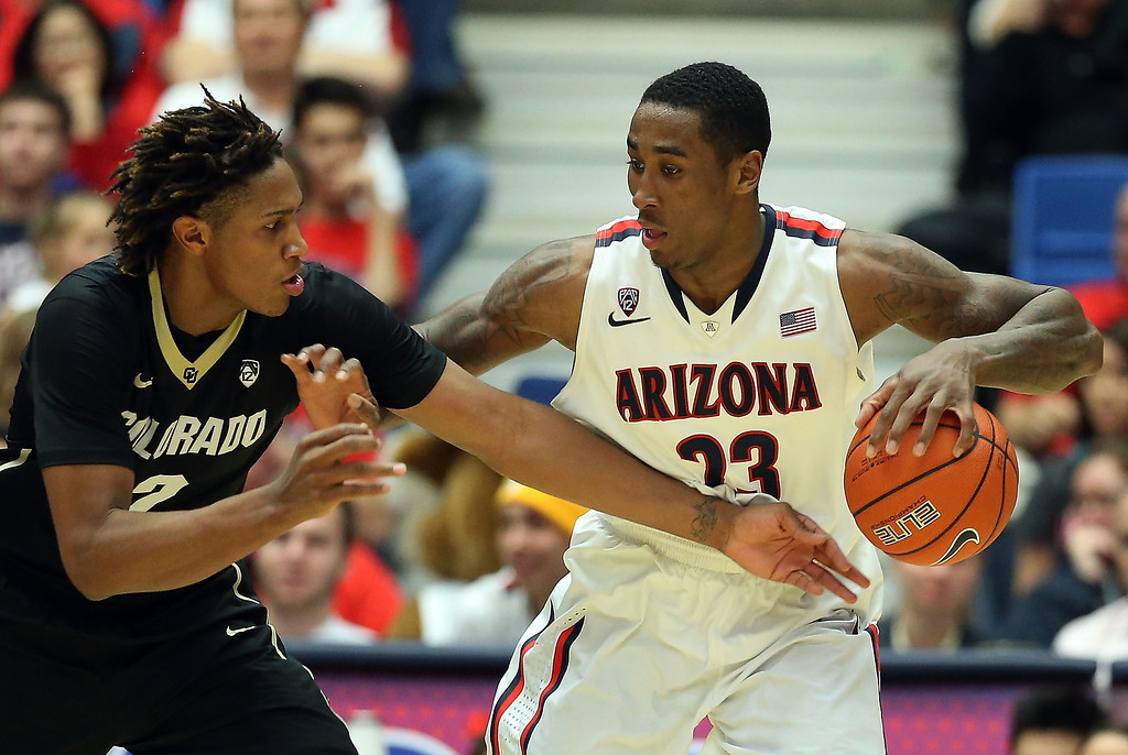 . Rondae Hollis-Jefferson #23 of the Arizona Wildcats handles the ball under pressure from Xavier Johnson #2 of the Colorado Buffaloes during the second half of the college basketball game at McKale Center on January 23, 2014 in Tucson, Arizona. The Wildcats defeated the Buffaloes 69-57.  (Photo by Christian Petersen/Getty Images)