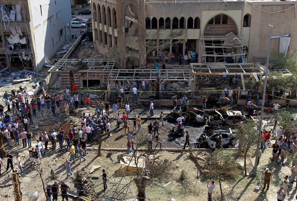 . People gather outside the Salam Mosque amid charred cars and wide damage, in the northern city of Tripoli, Lebanon, Friday, Aug. 23, 2013.  (AP Photo/Bilal Hussein)