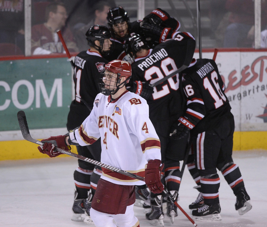 . DENVER, CO. - JANUARY 10: Pioneers\' defenseman Josiah Didier (4) skated past the Huskies as they celebrated a goal in the third period. The St. Cloud State hockey team defeated the University of Denver 6-3 at Magness Arena Friday night, January 10, 2014. Photo By Karl Gehring/The Denver Post