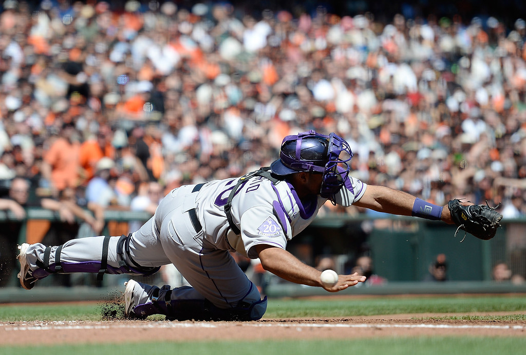 . Catcher Wilin Rosario #20 of the Colorado Rockies can\'t come up with the errant throw from third baseman Chris Nelson #4 which allowed Angel Pagan #16 of the San Francisco Giants to score in the bottom of the second inning at AT&T Park on April 10, 2013 in San Francisco, California.  (Photo by Thearon W. Henderson/Getty Images)