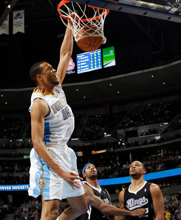 . Denver Nuggets forward Anthony Randolph, front, dunks the ball for a basket over Sacramento Kings forwards James Johnson, back left, and Chuck Hayes in the fourth quarter of the Nuggets\' 121-93 victory in an NBA basketball game in Denver on Saturday, Jan. 26, 2013. (AP Photo/David Zalubowski)