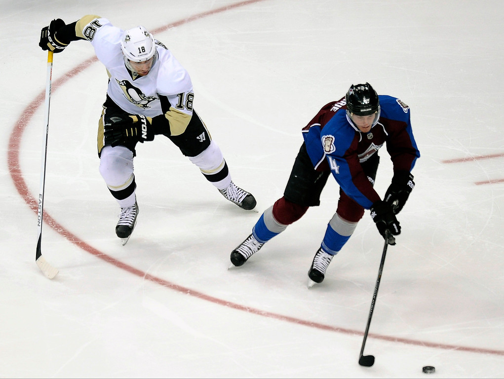 . Pittsburgh Penguins left wing James Neal, left, pursues Colorado Avalanche defenseman Tyson Barrie during the first period of an NHL hockey game Sunday, April 6, 2014, in Denver. (AP Photo/Chris Schneider)