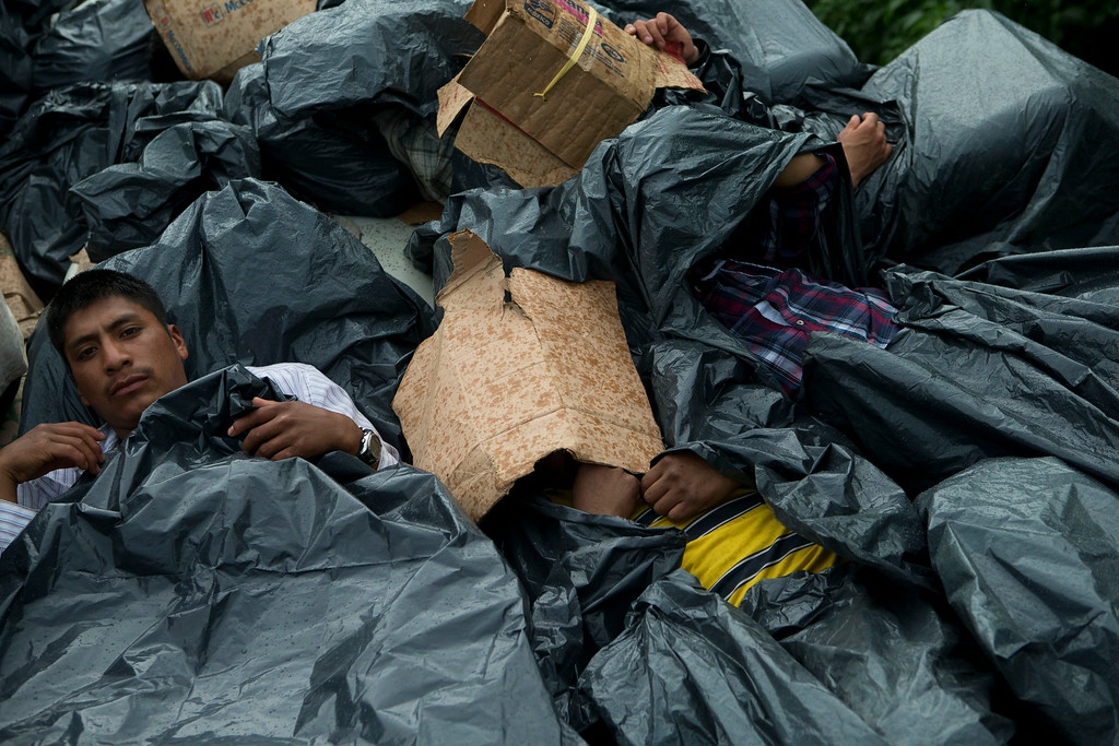 . In this Friday, June 20, 2014 photo, Central American migrants use trash bags and cardboard to protect themselves from the rain as they wait atop a stuck freight train, outside Reforma de Pineda, Chiapas state, Mexico. A vast majority of migrants interviewed along the primary migrant route said they were fleeing gang violence that has reached epidemic levels in Guatemala, Honduras and El Salvador in recent years. (AP Photo/Rebecca Blackwell)