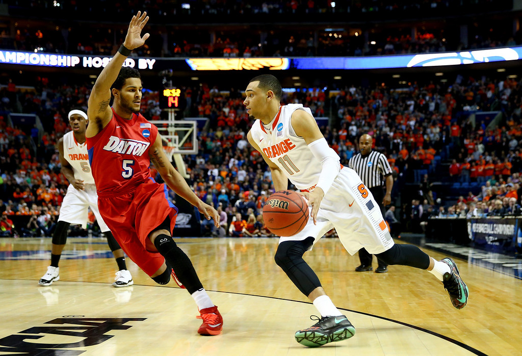 . BUFFALO, NY - MARCH 22: Tyler Ennis #11 of the Syracuse Orange drives to the basket as Devin Oliver #5 of the Dayton Flyers defends during the third round of the 2014 NCAA Men\'s Basketball Tournament at the First Niagara Center on March 22, 2014 in Buffalo, New York.  (Photo by Elsa/Getty Images)