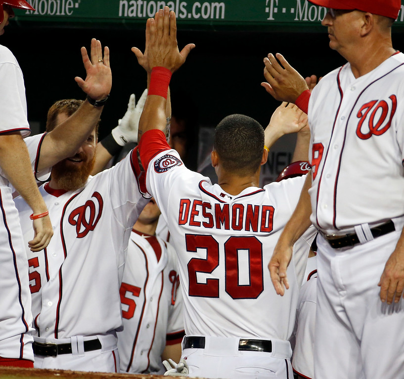 . Washington Nationals\' Ian Desmond (20) celebrates his solo home run with teammates during the seventh inning of a baseball game against the Colorado Rockies at Nationals Park, Wednesday, July 2, 2014, in Washington. The Nationals won 4-3. (AP Photo/Alex Brandon)