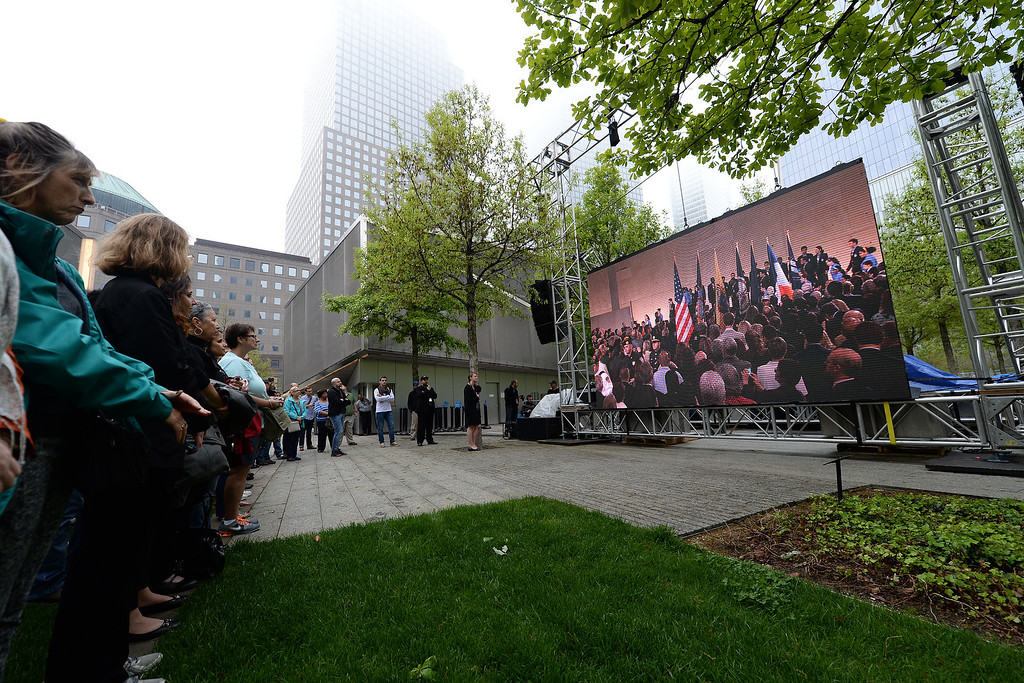 . Members of the general public watch a screen projection of U.S. President Barack Obama giving a speech during the dedication ceremony at the National September 11 Memorial Museum at ground zero May 15, 2014 in New York City.  (Photo by Anthony Behar-Pool/Getty Images)