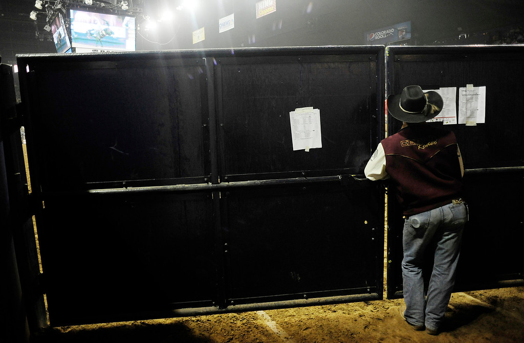 . A man peers through gates leading into the ring during the U.S. Bank Pro Rodeo Finals, at the National Western Stock Show in Denver, CO, Sunday, January 26, 2014. Sunday was the final day of the event.  (Photo By Brenden Neville / Special to The Denver Post)